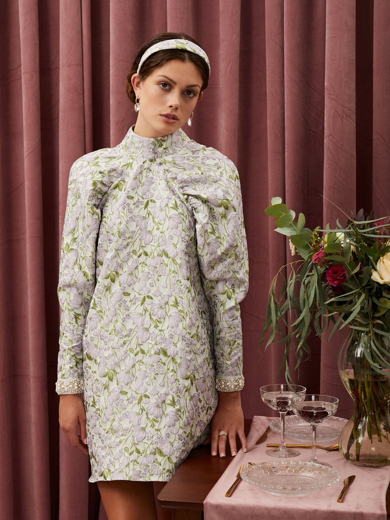 Sister Jane High neck mini dress in a floral jacquard fabric. Featuring full length raglan sleeves with embellished cuffs. This style is lined.