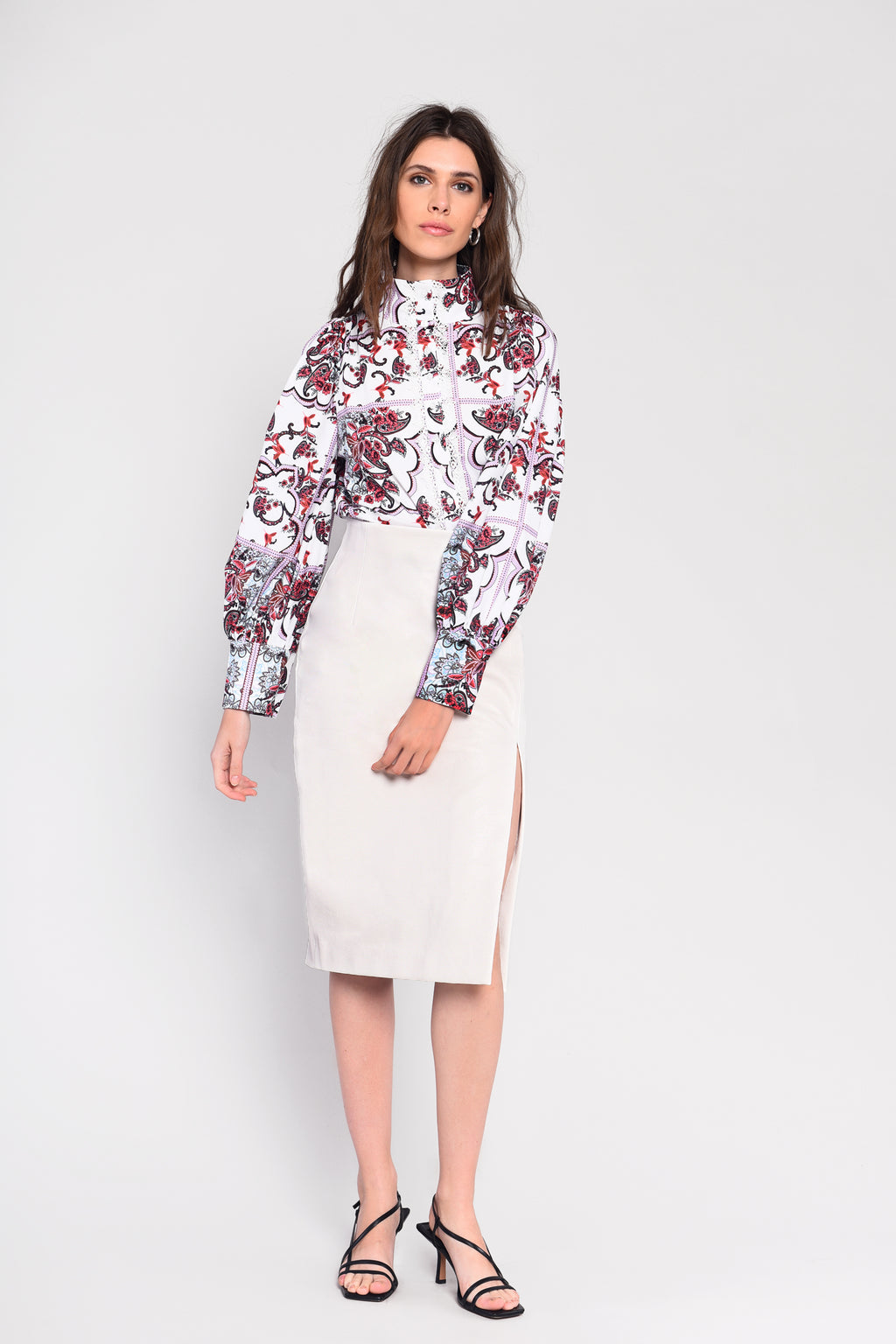 Glamorous white faux leather midi skirt featuring thigh split and back zip fastening.