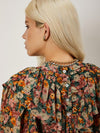 Ghospell Oversized green, yellow and orange floral blouse in a drapey floral printed fabric. Featuring a pleated neckline, detailed with ruffles.