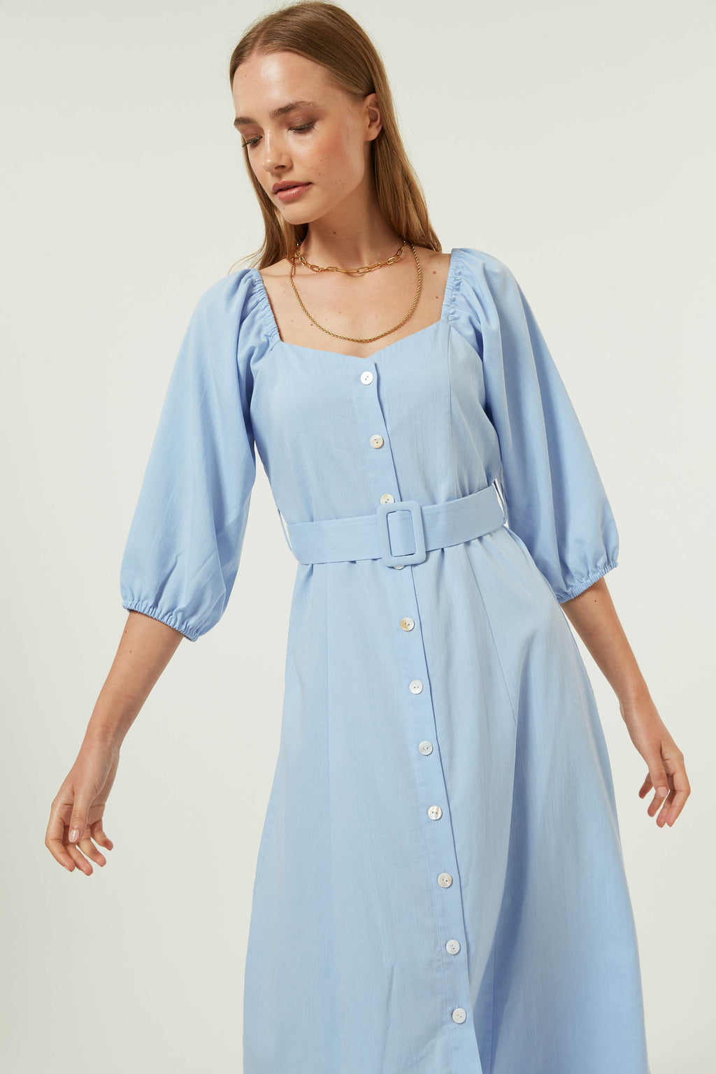 Jovonna London beautiful feminine off or on shoulder style midi dress featuring  button plackets fall to knee length, ¾ elastic sleeve, with a matching removable waist belt.