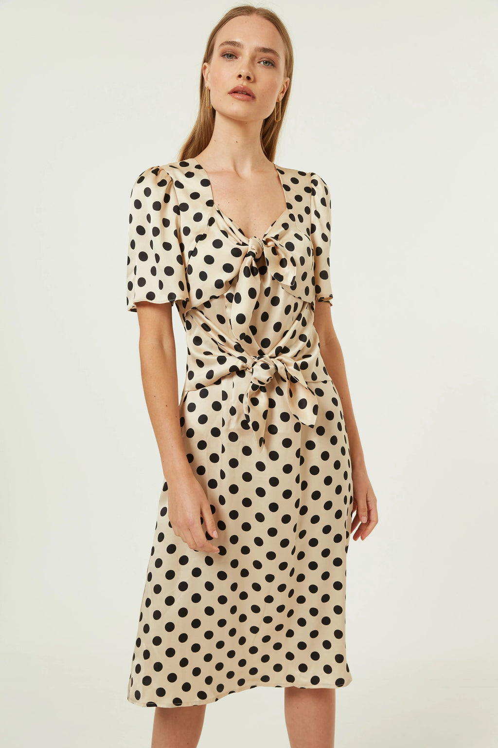 Jovonna London beige with black polka dot midi length dress in a relaxed fit with a subtle queen Anne neckline. Short sleeved with front tie details that can be tied to create a bow detail and cinch in waist.