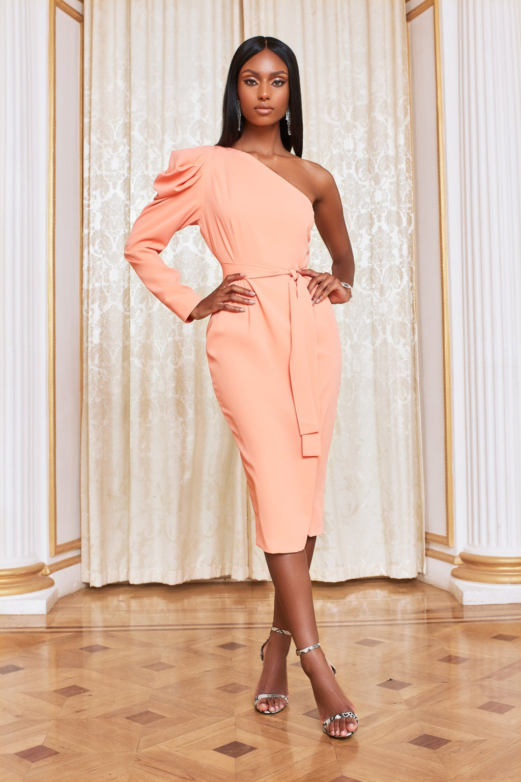 Lavish Alice cowl sleeve one shoulder midi dress in a soft shade of cantaloupe. Perfect statement dress for any occasion; wedding guest, communion, confirmation, party.  The tie waist shapes the body to create an hourglass silhouette.