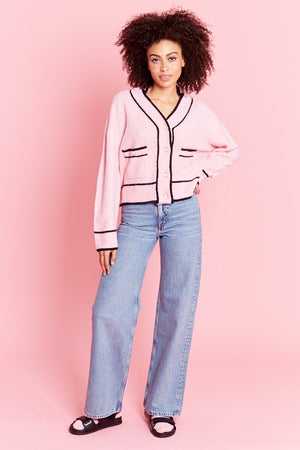 We're never wrong. This super soft Neon Rose pink cardigan is right on trend! Features front pockets,  button-down closure with crystal buttons, relaxed, cropped silhouette, and black trim edges.