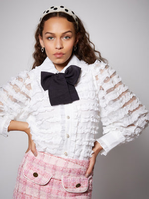 Sister Jane Rumba Ruffle Bow Blouse in a sheer ruffle spot fabric. Featuring a removable necktie in contrast fabric. Pearl buttons detail the front.