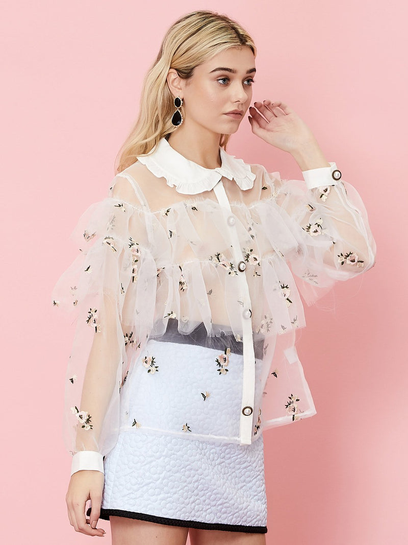 Dainty embroidered flowers adorn this stunning sheer top from iconic British clothing brand, Sister Jane. Features ornate pearl buttons, long sleeves and bib collar. (Does not come with undershirt.)
