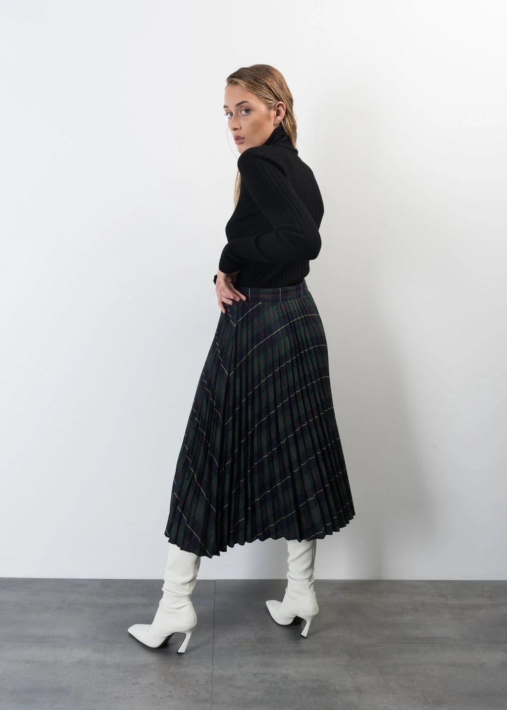 A bold structured tartan pleated midi skirt featuring curved hem which dips at the sides.