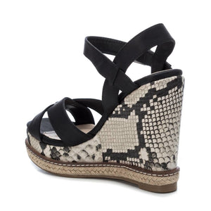 Women's on trend sandals with wedge lined in printed snake print from the Xti brand. Crossed straps on the instep. Buckle closure on the side. 12 cm wedge and 3 cm front platform. Rubber sole. A wedge with a lot of style to give an extra height to your look.