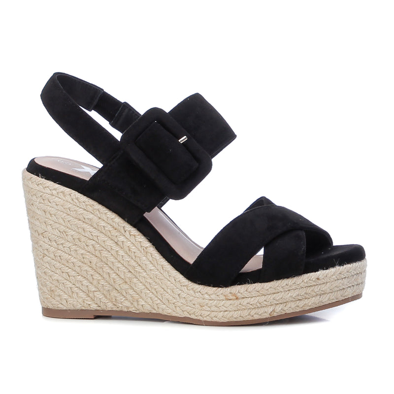 Women's on trend black faux suede sandals from the Xti brand. Crossed straps on the instep. Buckle closure on the side. 12 cm wedge and 3 cm front platform. Rubber sole. A wedge with a lot of style to give extra height to your look.