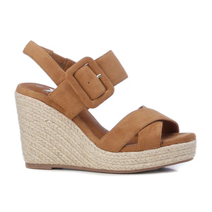 Women's on trend camel faux suede sandals from the Xti brand. Crossed straps on the instep. Buckle closure on the side. 12 cm wedge and 3 cm front platform. Rubber sole. A wedge with a lot of style to give extra height to your look.