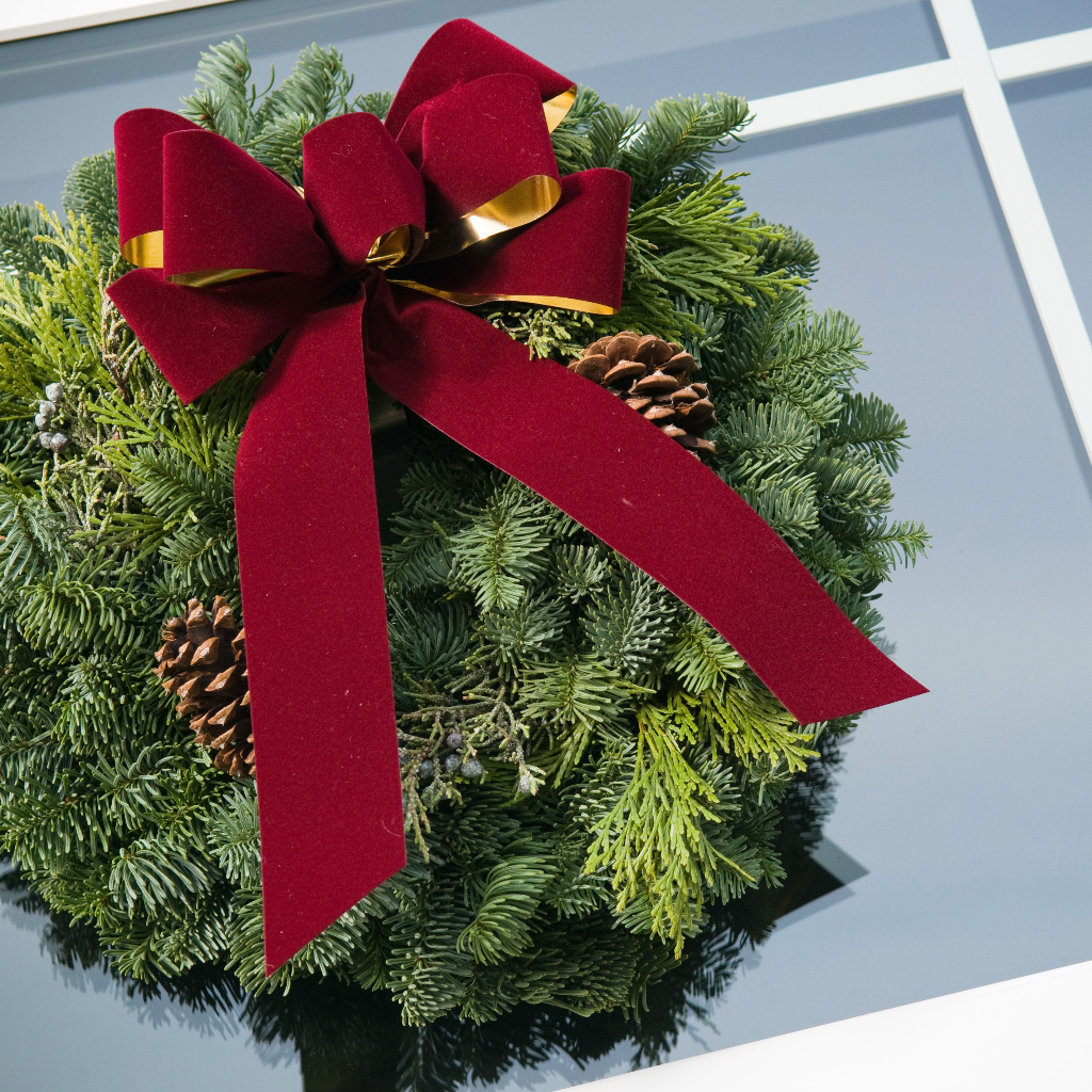 Christmas wreath of fir, cedar and juniper with pine cones and a gold-backed burgundy velveteen bow hung on a window