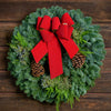 Christmas wreath of fir, cedar and juniper with pine cones and a gold-backed red velveteen bow on wooden background