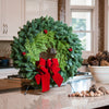Christmas wreath of fir and cedar with three red berry clusters and a gold-backed red velveteen bow on kitchen counter