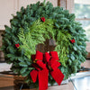 Christmas wreath of fir and cedar with three red berry clusters and a gold-backed red velveteen bow close up