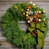 Fall wreath of pine, salal, pine cones, faux maple leaves, pumpkins, bronze balls and moss green bow close up
