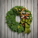 Fall wreath of pine, salal, pine cones, faux maple leaves, pumpkins, bronze balls and moss green bow on wooden background