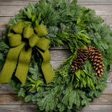 Christmas wreath with bay leaves, pine cones and a moss green brushed linen bow close up on wooden background