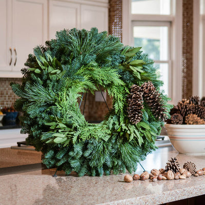 Christmas wreath with bay leaves, pine cones with no bow close up on a kitchen counter
