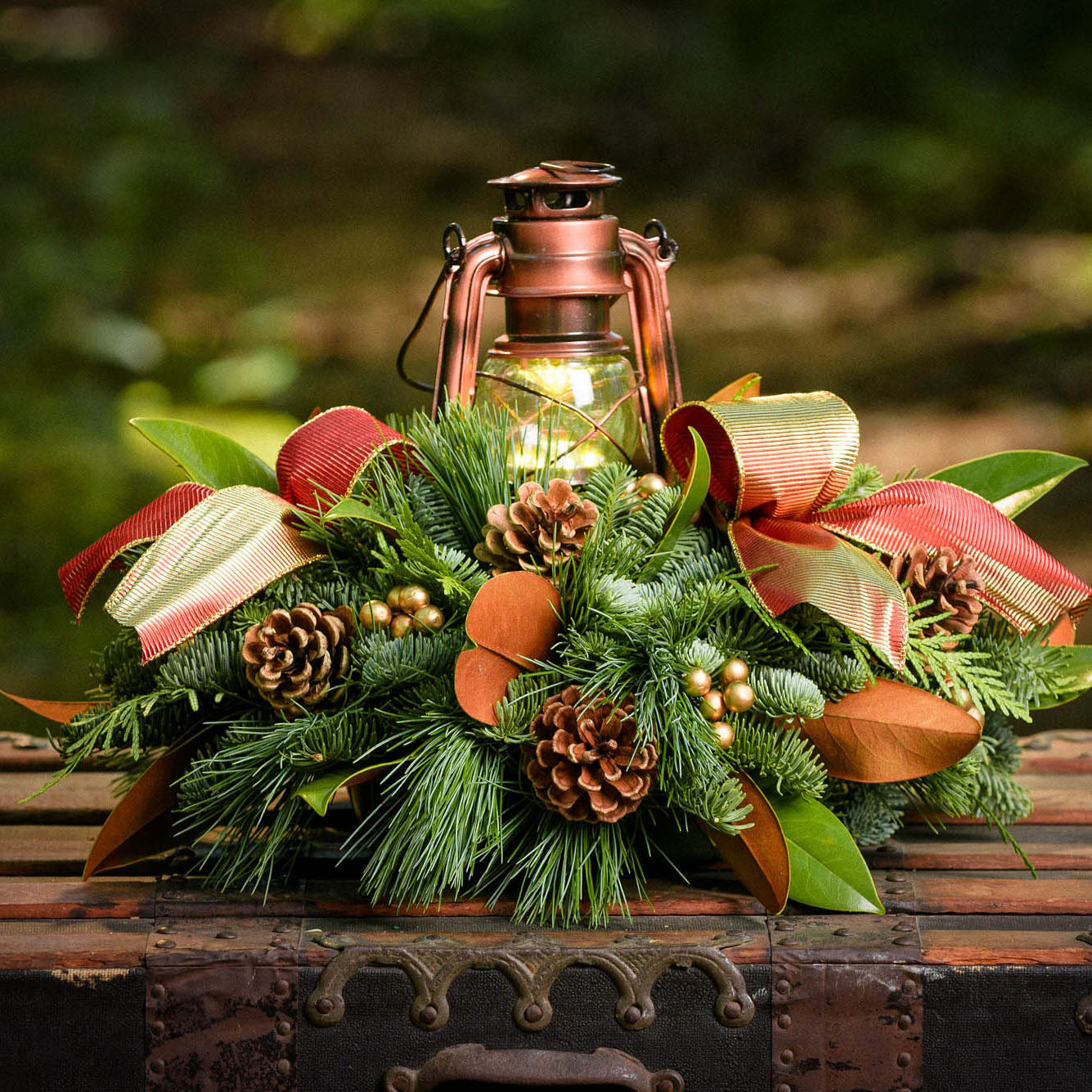 Centerpiece with magnolia leaves, pine cones, gold ornaments and a shimmery red-gold bow and a bronze LED lantern up close