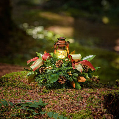 Centerpiece with pine cones, gold ornaments and a shimmery red-gold bow and a bronze LED lantern on a mossy log in the woods