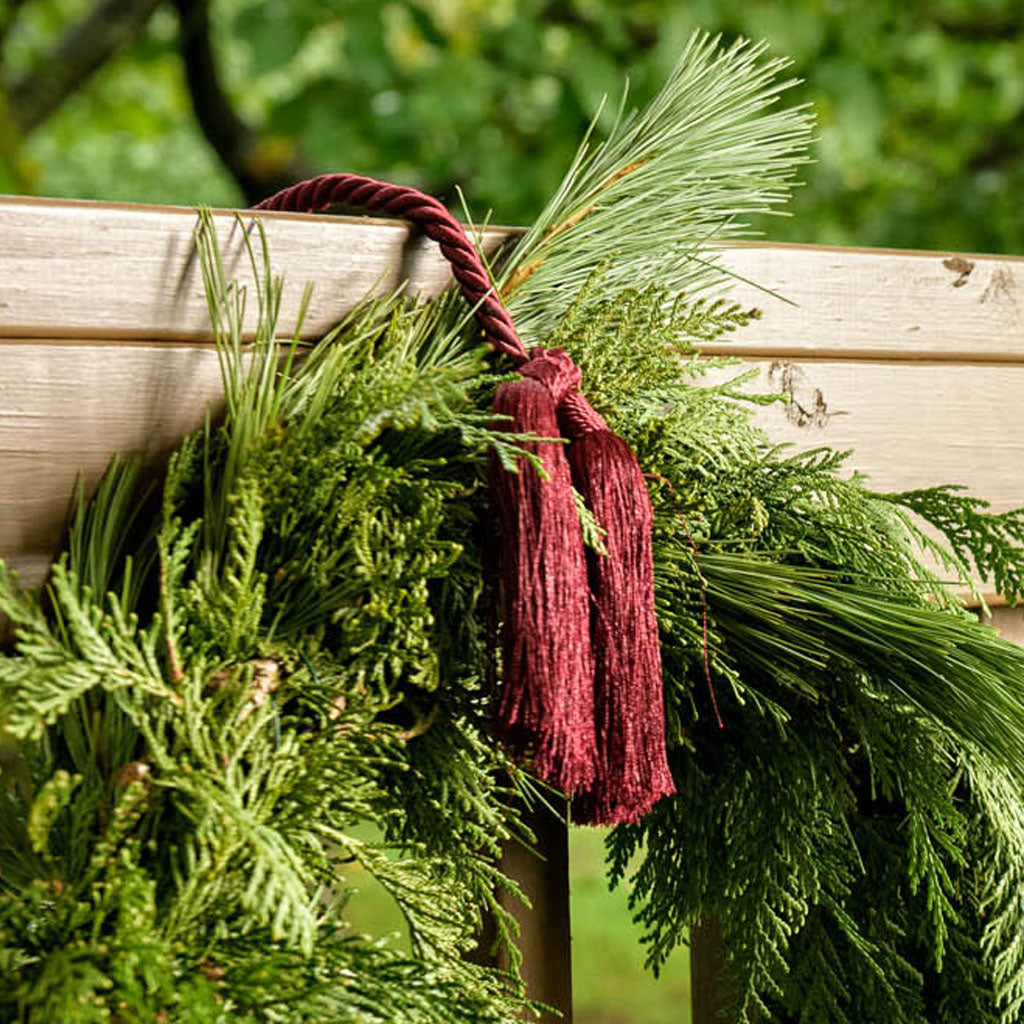 Burgundy garland tie holding garland on wooden railing