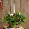 Charming centerpiece in a wooden barrel with holly, pine cones, white berries and a white taper candle close up