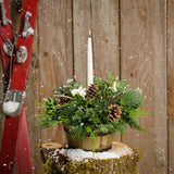 Charming centerpiece in a wooden barrel with holly, pine cones, white berries and a white taper candle on snowy tree stump