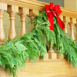 Western red cedar garland hanging from banister with red velvet bow