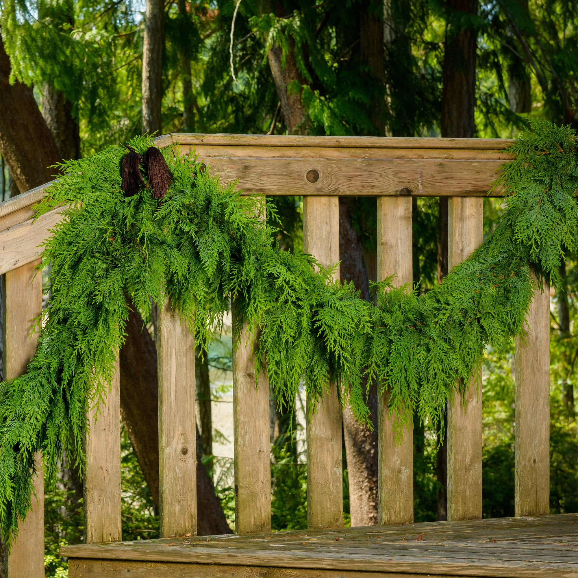 Western red cedar garland hanging from banister with chestnut garland tie