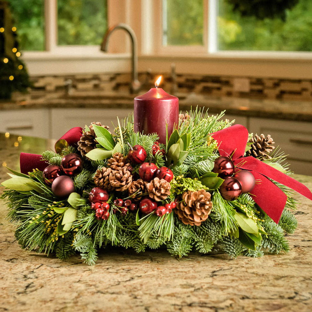 Christmas centerpiece with pine cones, bay leaves, apples and berries and burgundy velveteen bows on kitchen counter