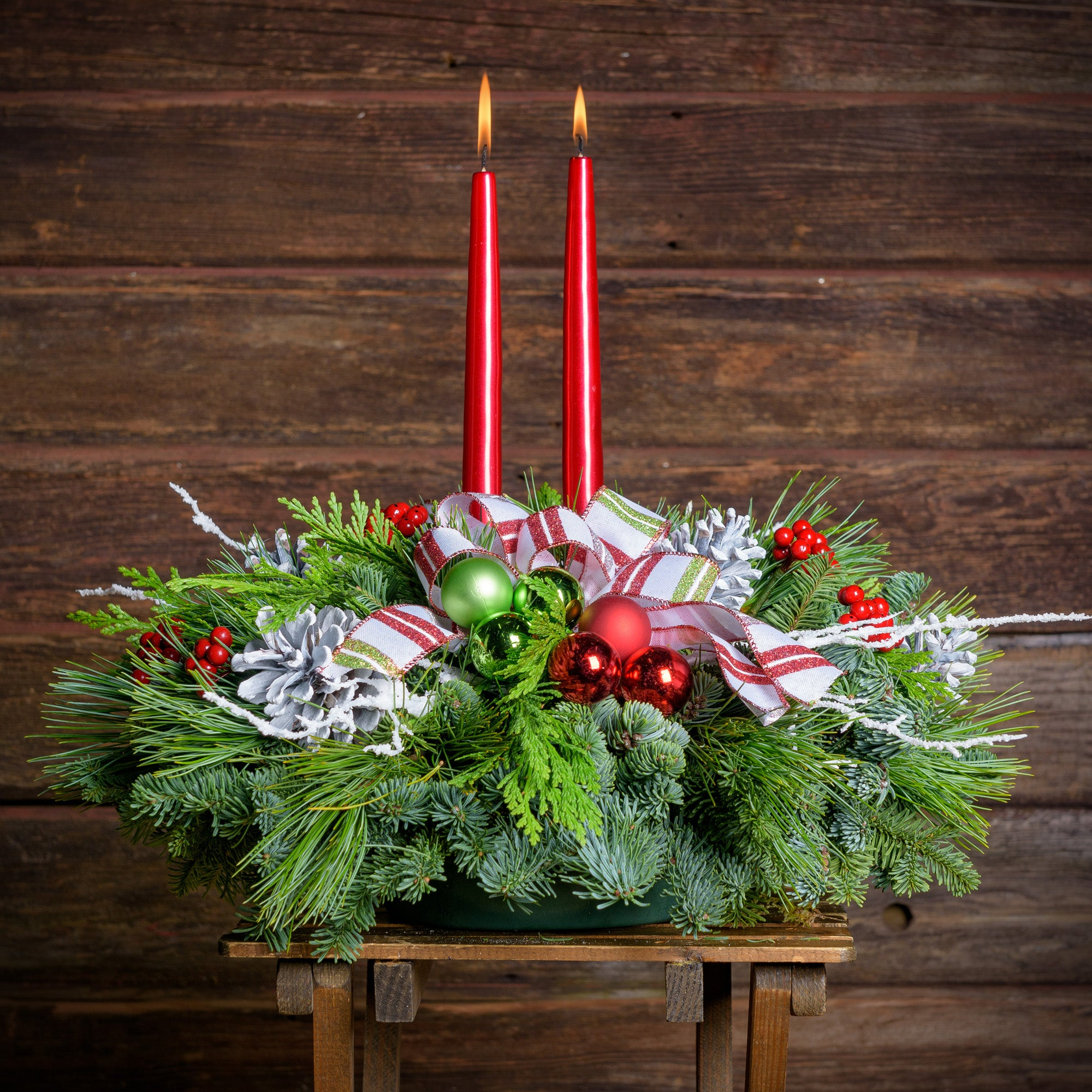 Evergreen Centerpiece with white pine cones, red berries, white twigs, red & green balls & a red & white glitter-striped bow