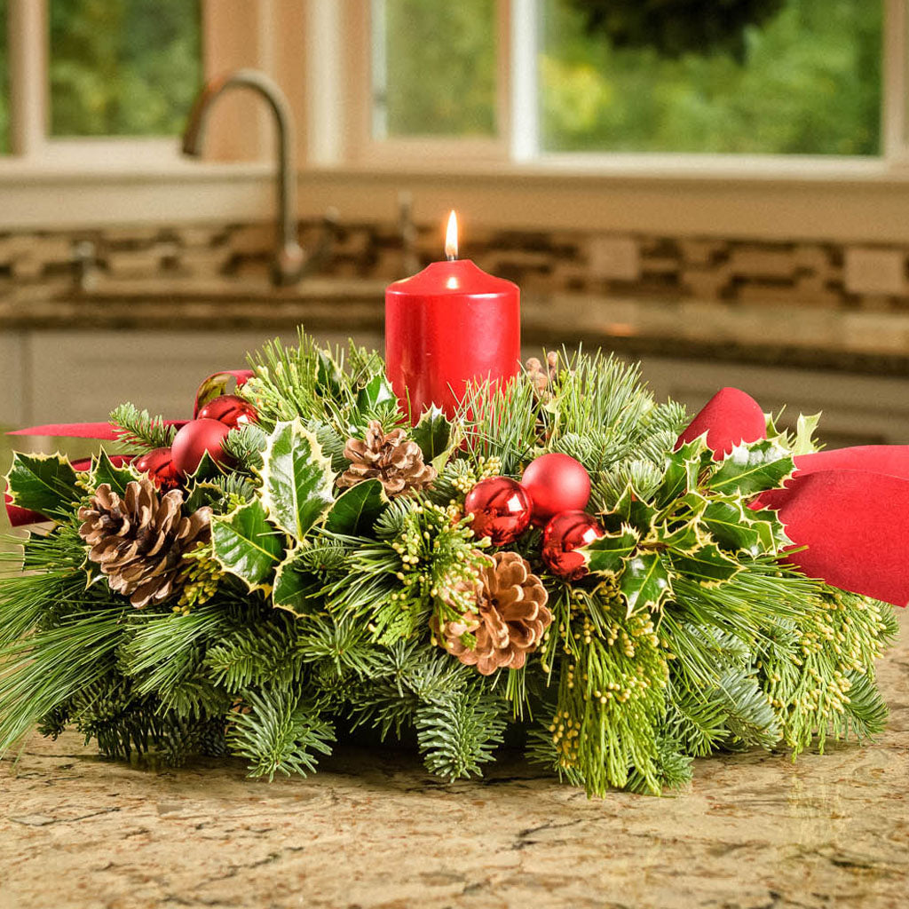 Christmas centerpiece with holly, pine cones, red ornaments and a red pillar candle displayed on a kitchen counter
