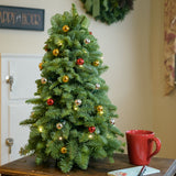 Fresh hand assembled tabletop Christmas tree made of noble fir and red, silver and gold balls.