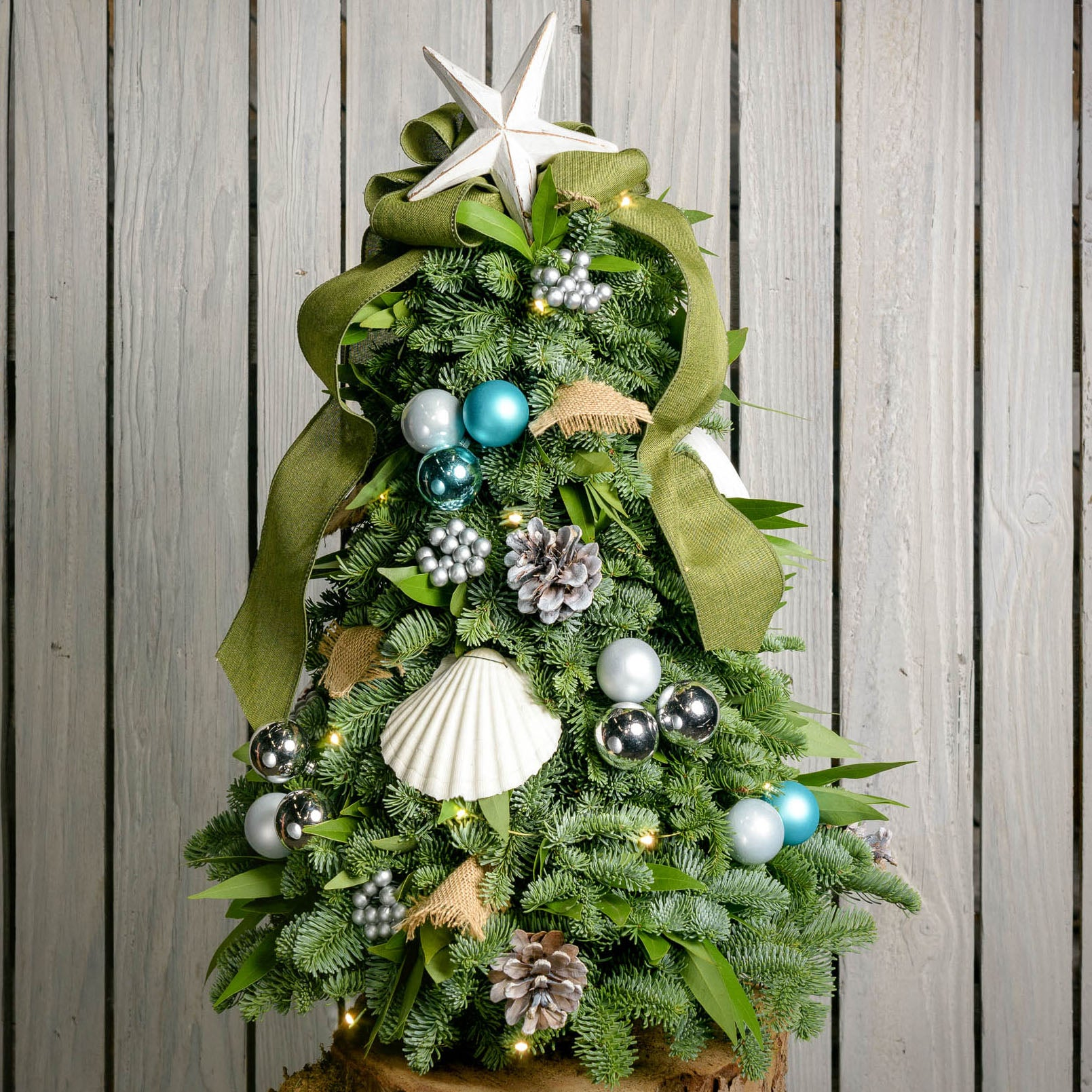 Fresh hand-assembled tabletop Christmas tree with seashells, star, pine cones, aqua and silver balls berries green burlap bow