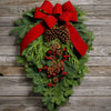 Christmas Swag made with fir cedar juniper pine cone glittery branches silver balls and red bow on wooden background