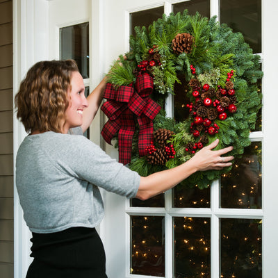 Christmas wreath made with pine cones, apples and berries and a red and black plaid bow being hung on a door by a woman