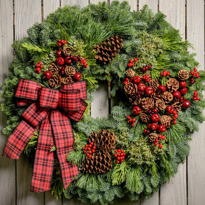 Christmas wreath made with fir, pine, cedar, juniper, pine cones, apples and berries and a red and black plaid bow close up