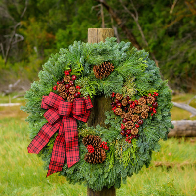 Christmas wreath made with fir, pine, cedar, juniper, pine cones, apples & berries & a red and black plaid bow on wood post