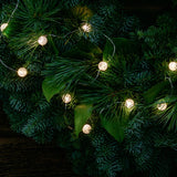 White, globe shaped, cracked glass effect battery operated lights on a evergreen wreath close up illuminated