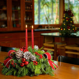 Evergreen centerpiece with white pine cones, red berries & ball clusters, 2 white trimmed red bows & two red tapers on table