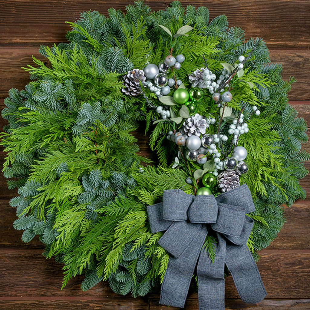 Winter wreath with silver and green balls, ornaments and branches with a grey brushed linen bow on cedar and fir base