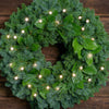 White, globe shaped, cracked glass effect battery operated lights on a evergreen wreath