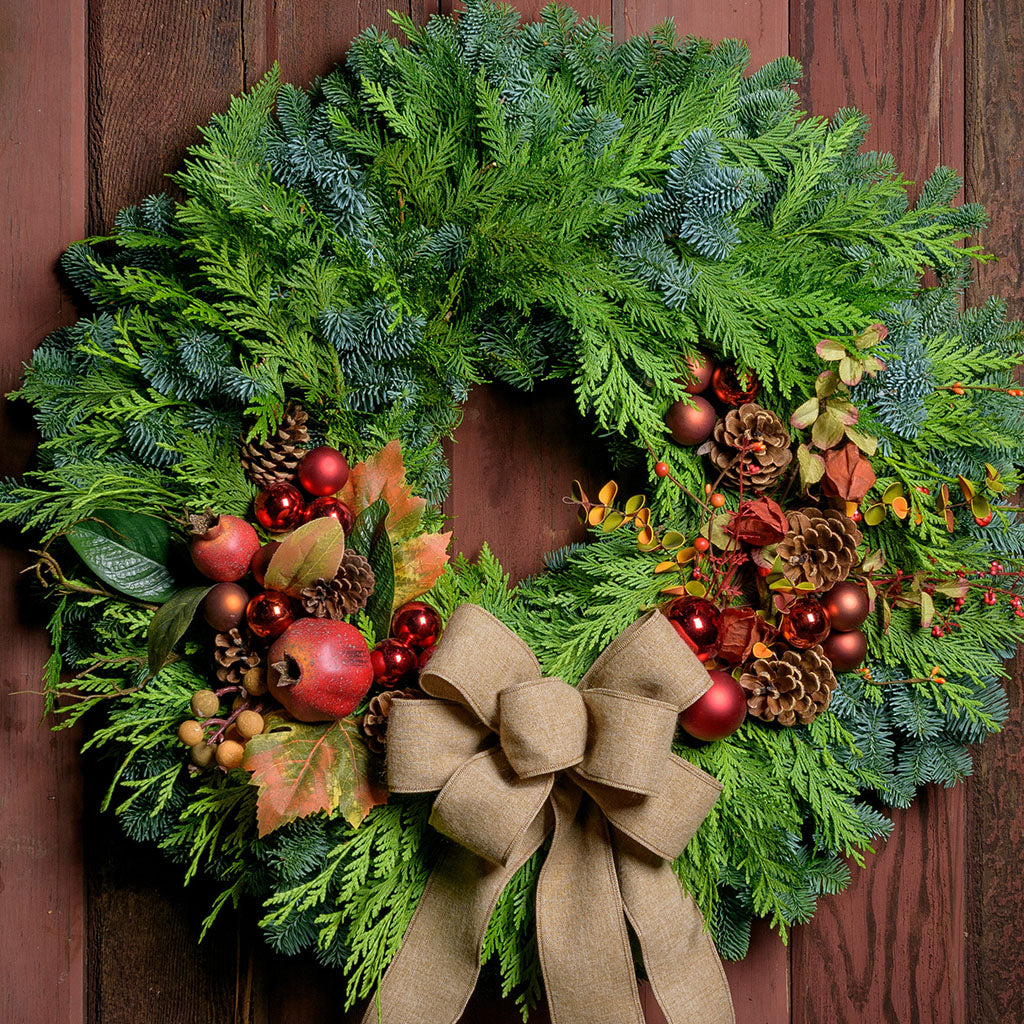Autumn wreath with fall leaves, pomegranates, copper and red balls on fresh evergreen base with a tan linen bow