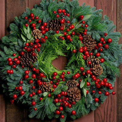 Christmas wreath with metallic red berries, pine cones, bay leaves on fir, pine and cedar base