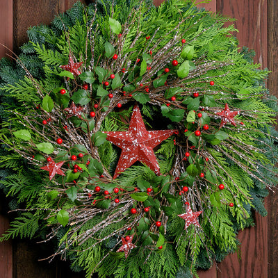 Farmhouse holiday Christmas wreath with speckled red, rustic stars, berries, holly and twigs on a base of noble and cedar