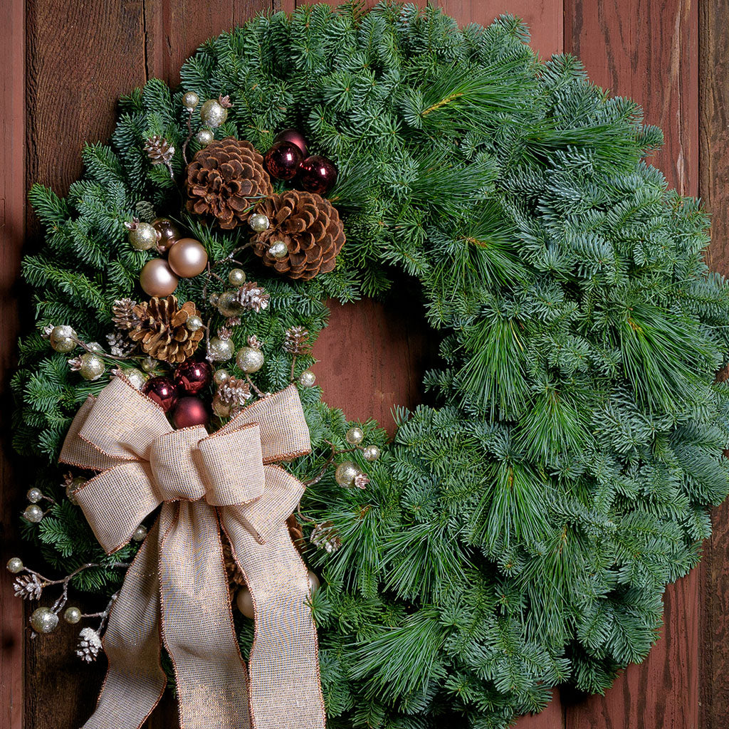 Wreath with pine cones, burgundy and champagne balls frosted snowberry twigs and an ivory bow with copper edges