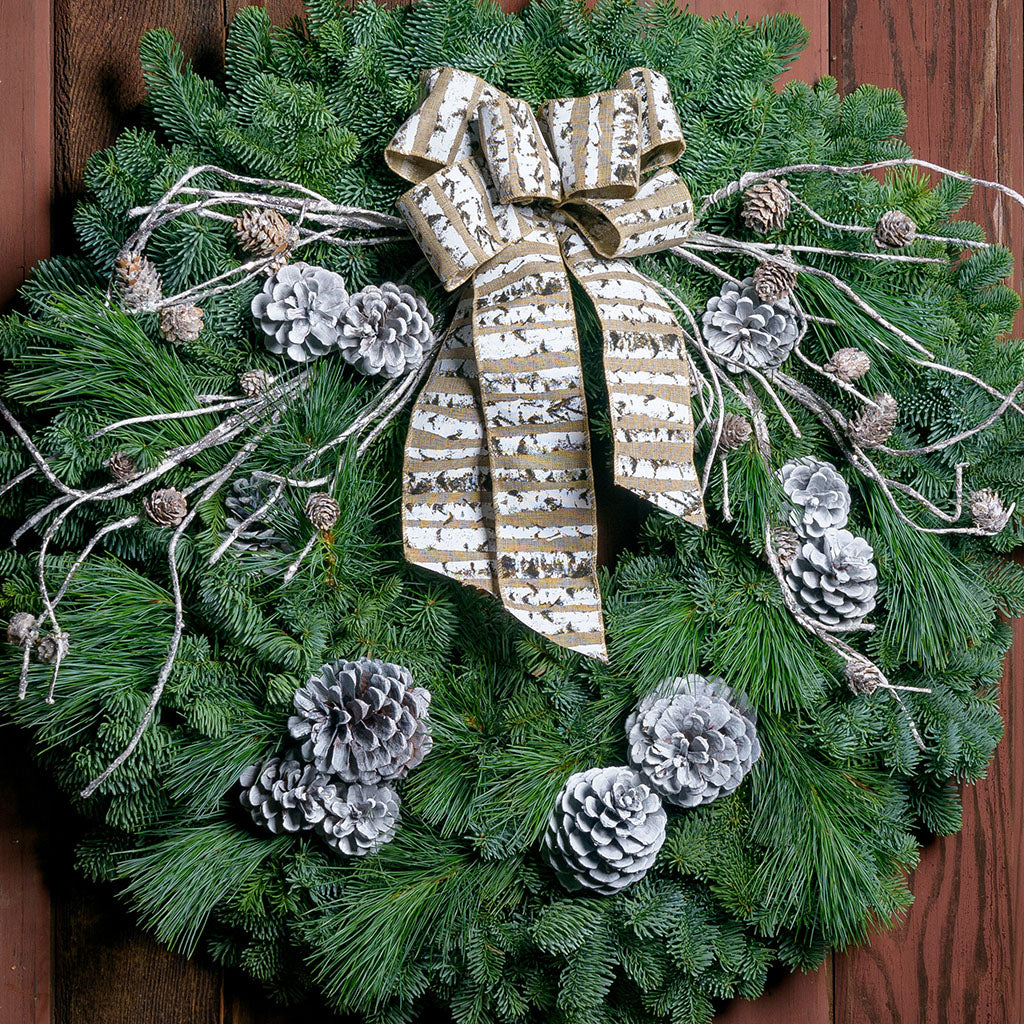 Winter wreath with silver glitter frosted branches, white pine cones, and a birch bark patterned bow on fir and pine base