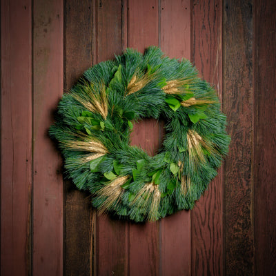 Autumn evergreen wreath made with pine, salal leaves and bearded wheat clusters on a wooden background