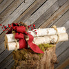 Three real birch logs tied with rope red line bow pine cones and red berries close up