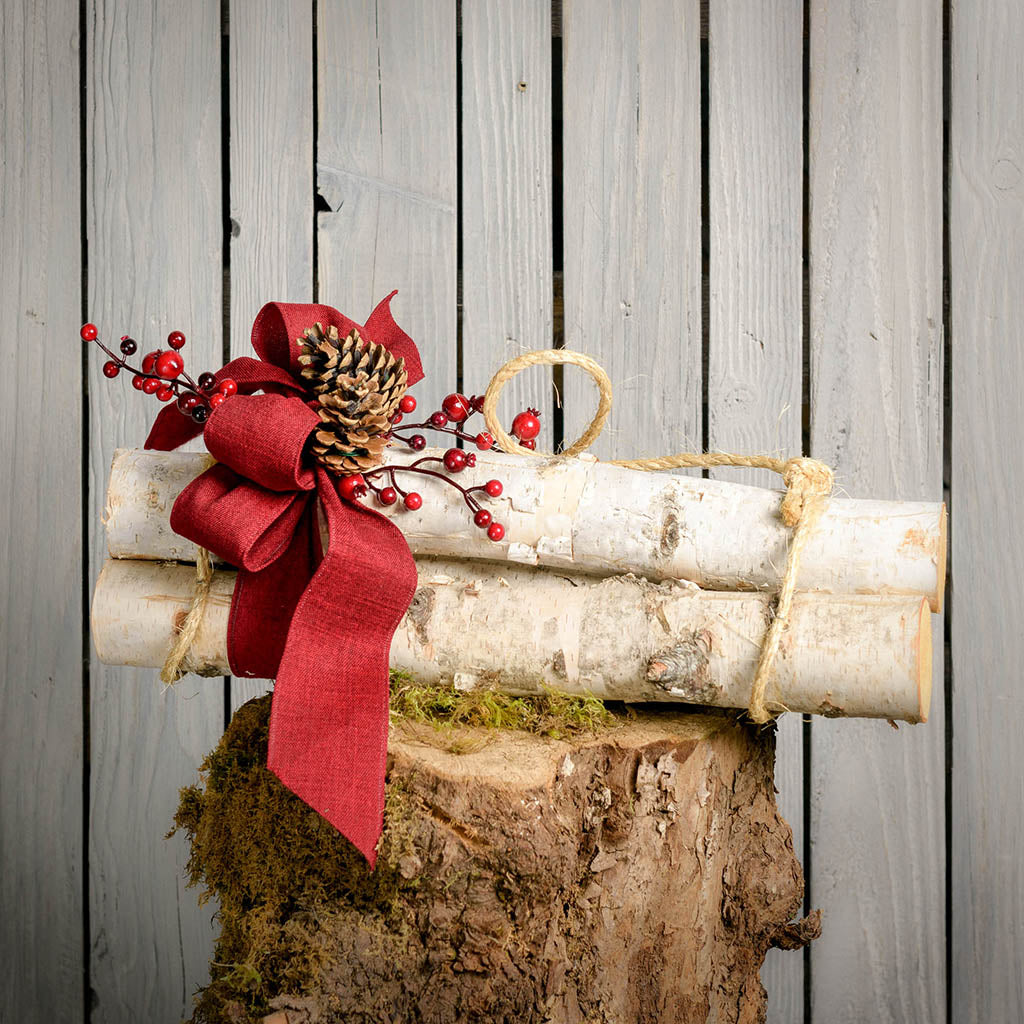 Three real birch logs tied with rope red line bow pine cones and red berries on a tree stump with wooden background