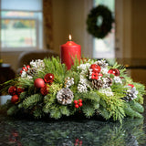 Frosted Christmas centerpiece with frosty pine cones, red ball, apples and berries and a red pillar candle up close